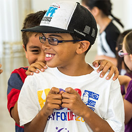 A student in a cap smiles as another student puts their hands on their shoulders from behind.