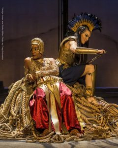 Veralyn Jones as Hera is lounging and Trisha Miller as Athena is sharpening her sword beside her. Photo is from Argonautika.
