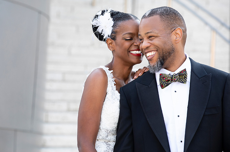 Kelsey Scott in her wedding gown and Malik B. El-Amin in a tuxedo and multi-colored bow tie on their wedding day.