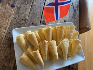 A mini Norway flag, which is red with a navy blue cross outlined with white, stands on a wood table next to a plate of beige krumkake cookies decorated with intricate hearts and rolled into cones.