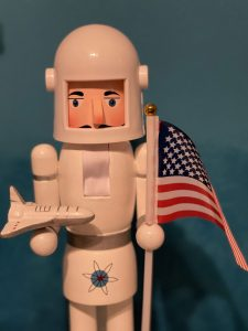 A nutcracker in a white astronaut suit stands in front of a blue background. The nutcracker holds an American flag in one hand and on the other hand holds a narrow white and silver space ship with three fins.