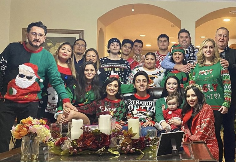 Erika Soto's family of all ages wearing ugly Christmas sweaters in green and red and blue colors, including one with Santa wearing sunglasses, one with Snoopy asleep on his doghouse, and several with an elf body with a green suit and red collar.