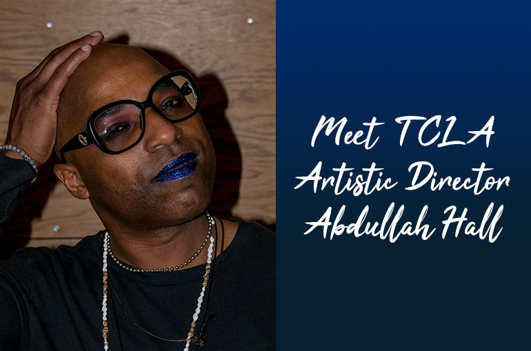 Meet TCLA Artistic Director Abdullah Hall. Abdullah is a Jamaican Pakistani person wearing a black long-sleeved shirt, large round glasses, purple eyeshadow, and blue lipstick. They rest their hand atop their head as they pose int front of a dark wood backdrop.