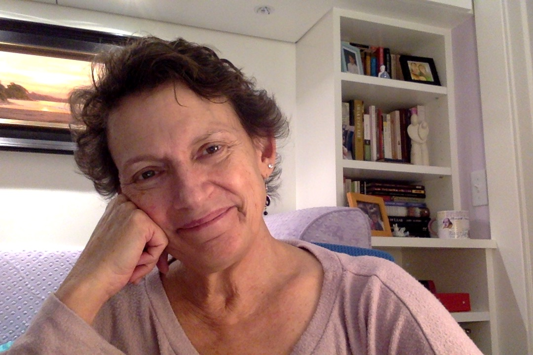 Miranda has short curly brown hair and wears a mauve shirt as she leans her head against her hand and smiles. She is sitting in a brightly lit white room with a bookshelf behind her.