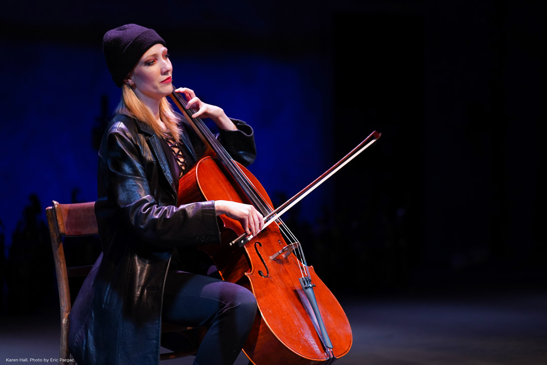 A blond woman wearing a black beanie and long black leather jacket and red lipstick and eyeshadow plays a cello as she sits in a wooden chair.