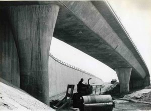 A black and white photo of a construction worker in a hard hat operating a steam roller under a bridge of the 210 freeway.