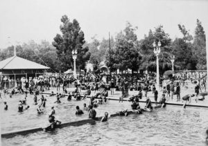 A black and white photo of the Brookside Plunge pool with large crowds of people swimming and playing and walking around. Several lampposts pepper the backdrop and large trees dominate the background landscape.