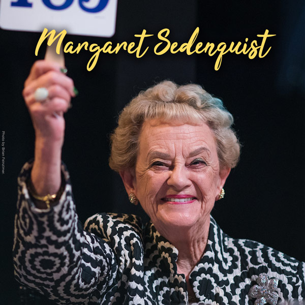 Margaret Sedenquest in yellow cursive. Margaret Sedenquist pictured at Dinner On Stage as she smiles and holds up a paddle. She has short curly blond hair with a green streak and wears a coat with black and white flowers.