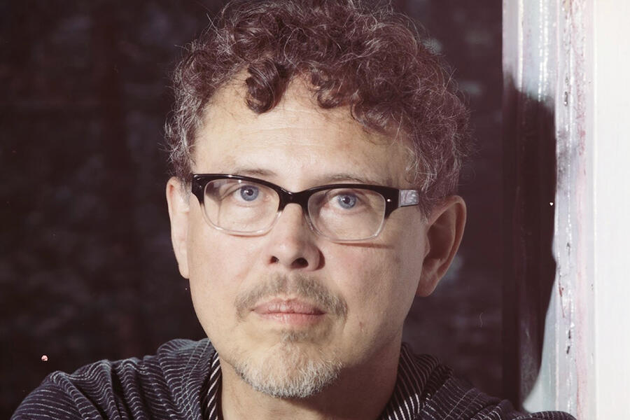 Jose Rivera has brown curly hair and faint mustache and beard and wears black rimmed glasses.